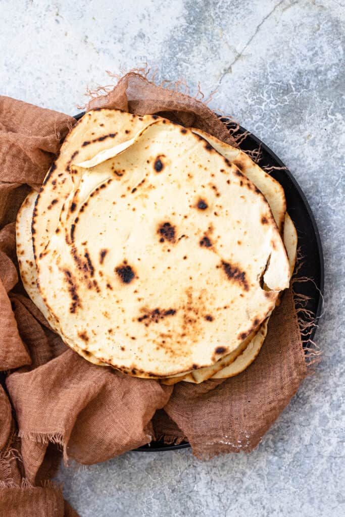 piles of tortillas on a black plate with a brown linen