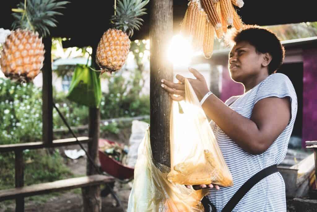 Fijian woman buying corn and pineapples