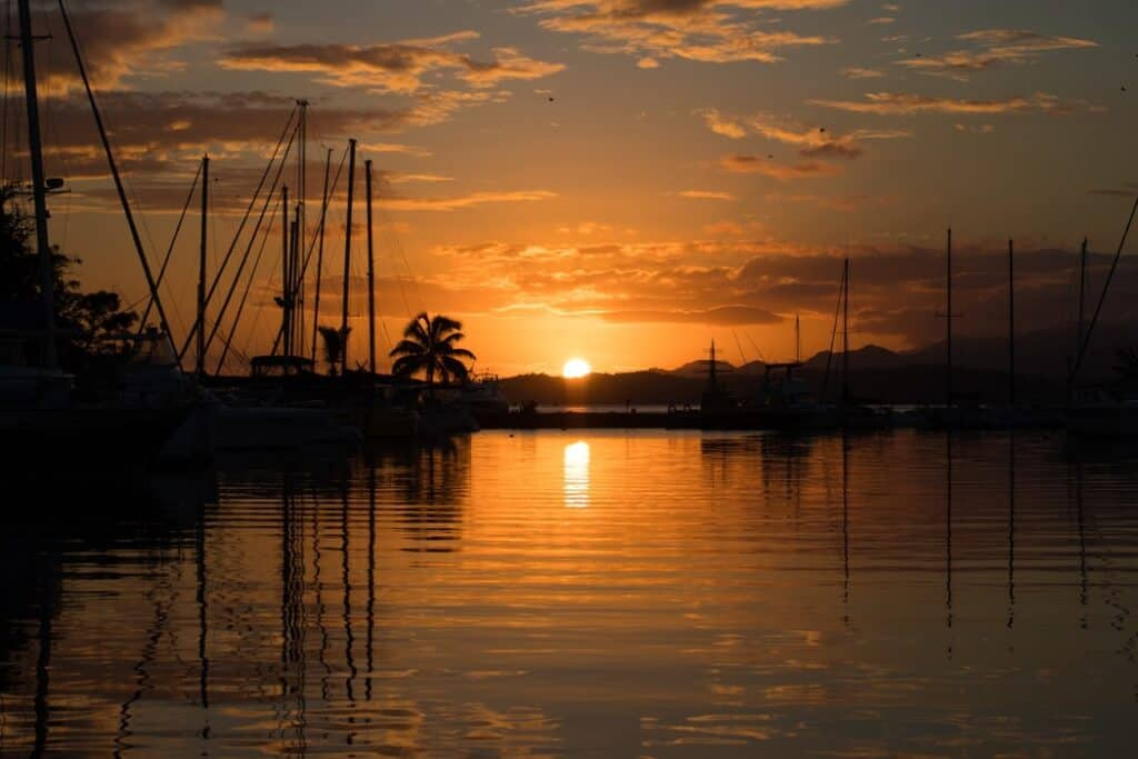 sunset over the water and sailboats