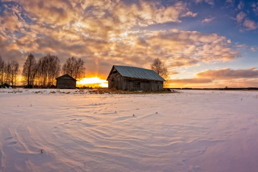 wood barn with a sunrise behind it