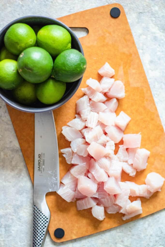 Mahi Mahi on a cutting board with fresh limes next to it