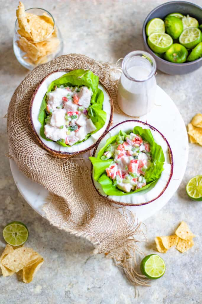 Ceviche with milk, coconut halves, limes, and tortilla chips