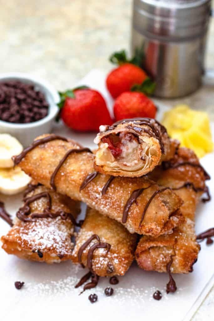 pile of banana split egg rolls with one cut in half on top