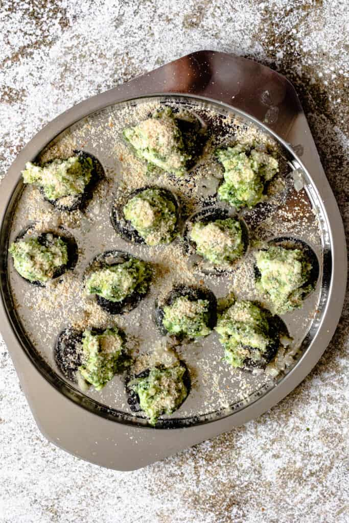 Snails in an escargot pan topped wit parsley butter and breadcrumbs