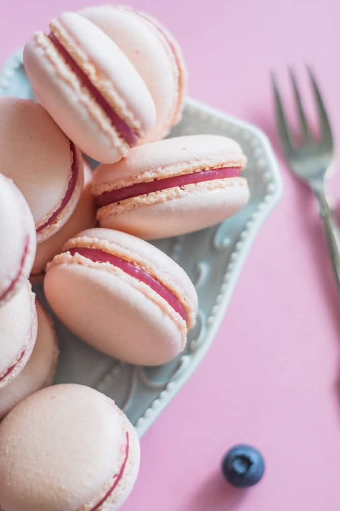 a pile of pink macarons with pink filling