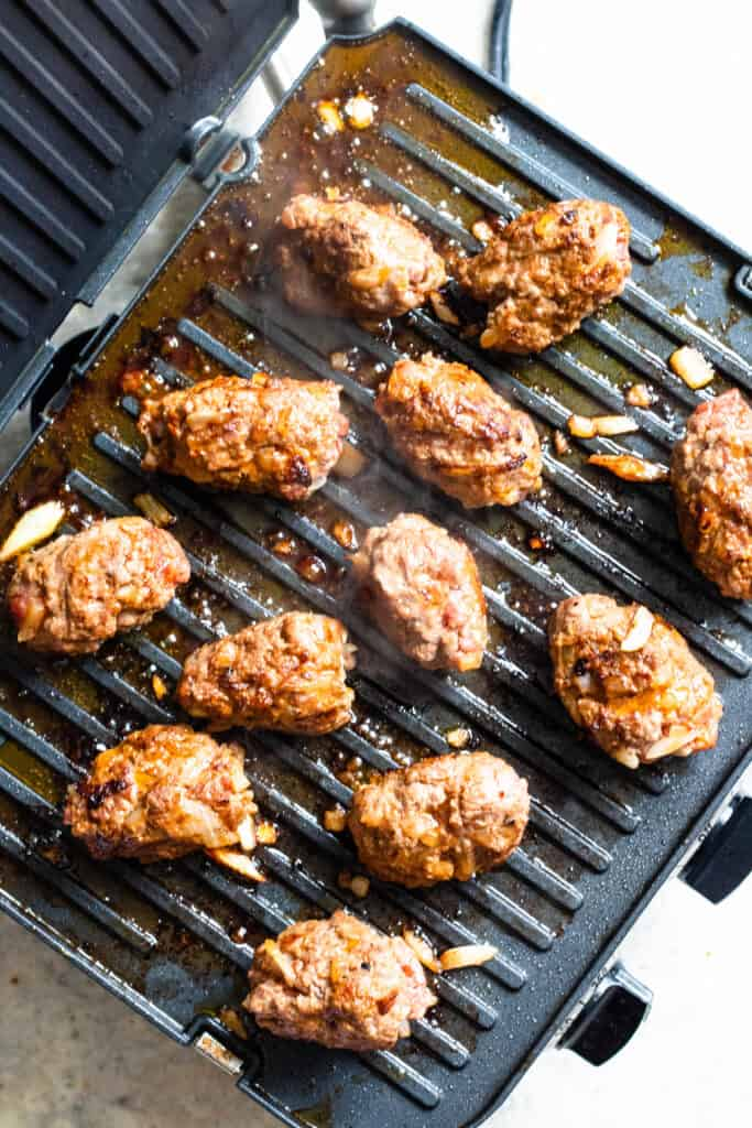 Cooking cevapi on a grill