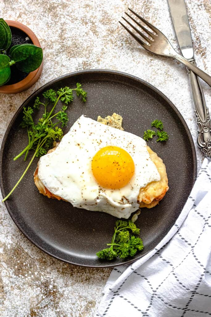 Croque madame on a black plate surrounded with parsley