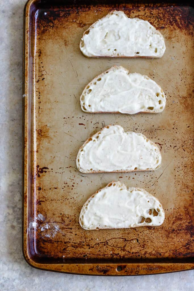 4 pieces of bread on a cookie sheet spread with bechamel sauce