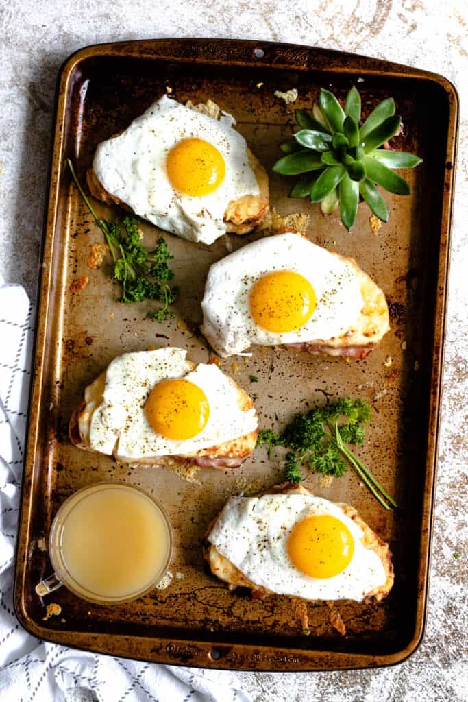Cookie sheet with 4 fully assembled croque madames with pineapple juice and parlsey on the side