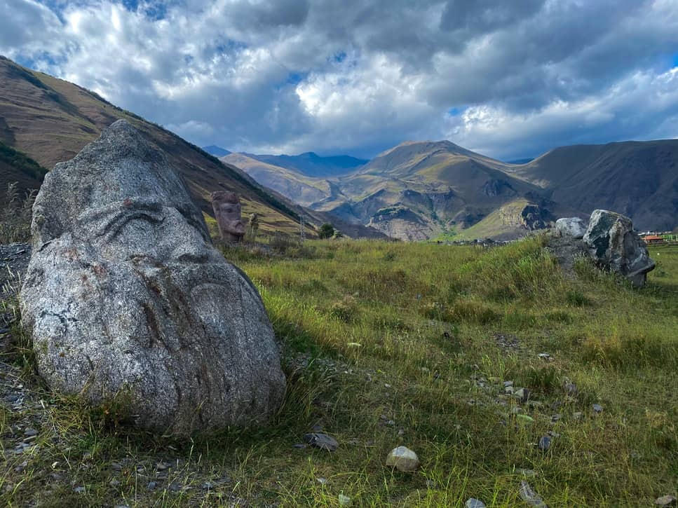 Face in stone boulders next to mountains