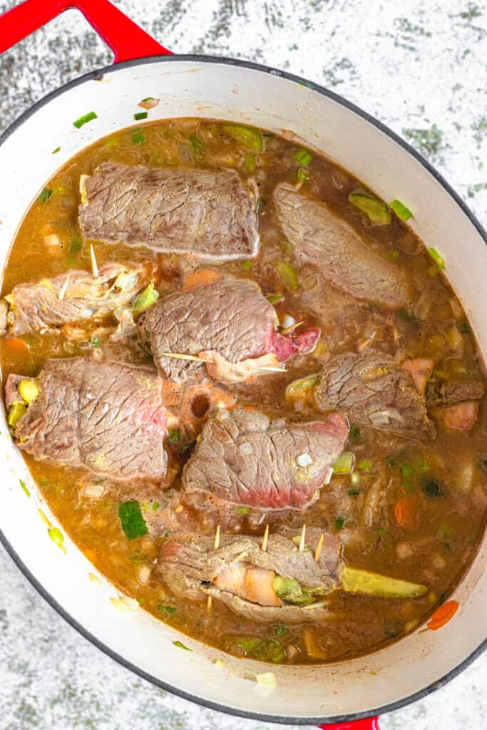 rolled beef simmering in a gravy sauce