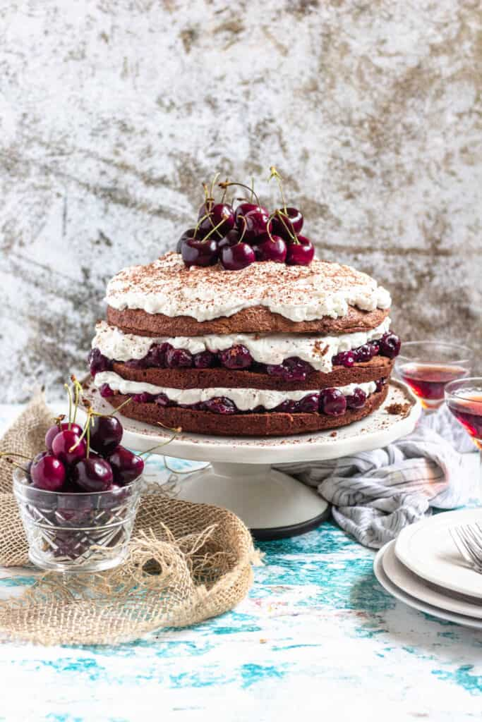 Black forest cake with cherry filling and whipped cream topping, surrounded by cherry liquor and cherries
