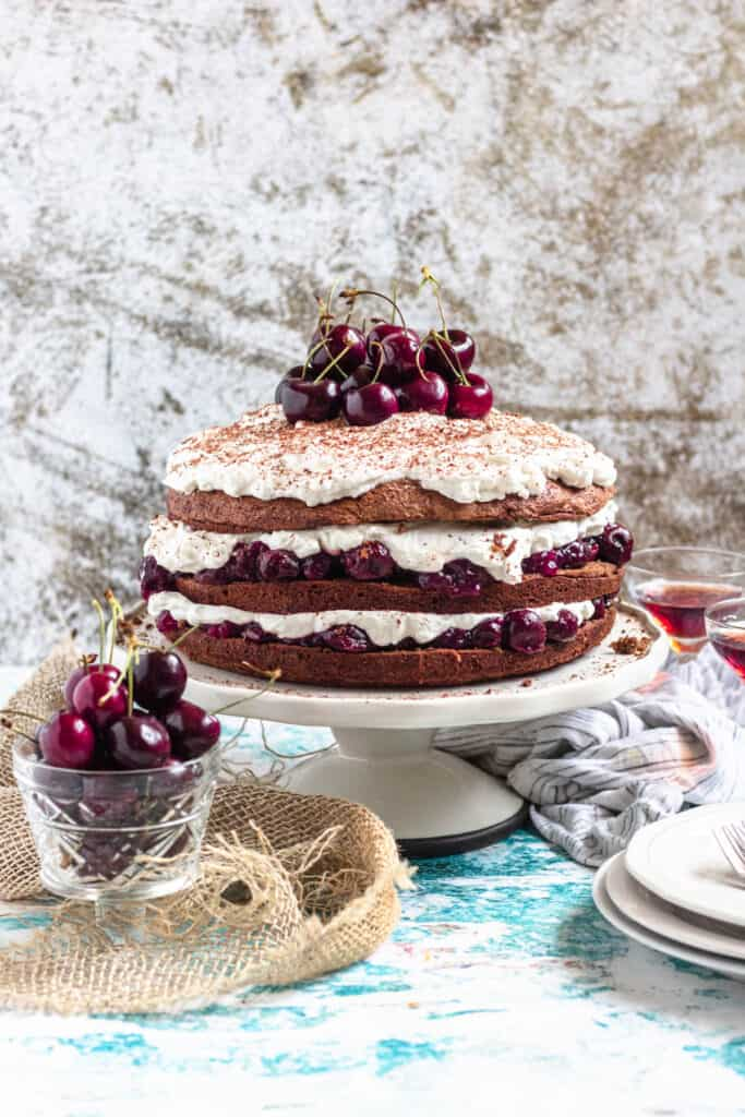 Black forest cake dripping with cherries and whipped cream