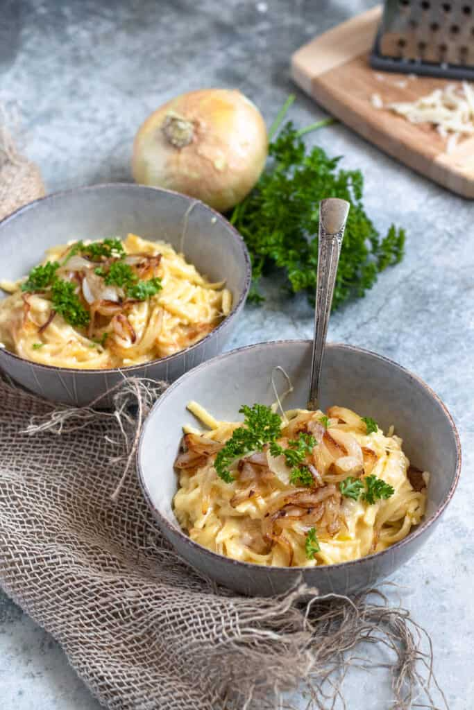 Bowl of cheese spatzle with parsley and onion