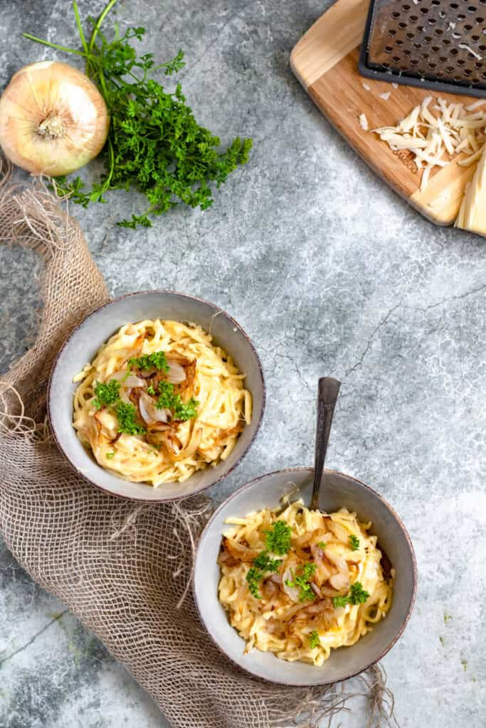 two bowls of cheese spaetzle with grated cheese and onions behind it