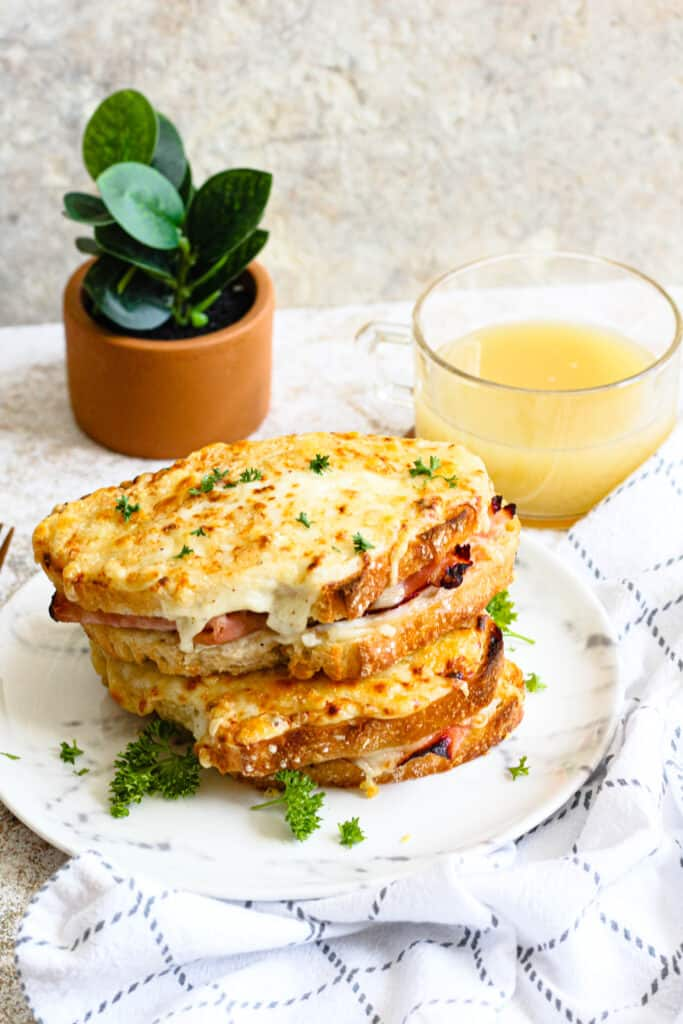 stack of croque monsieur sandwiches with orange juice behind it