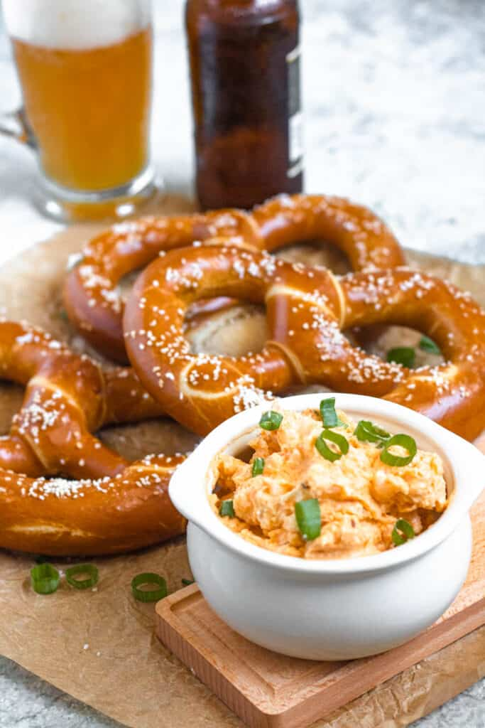 obatzda in a bowl with the soft pretzels in front
