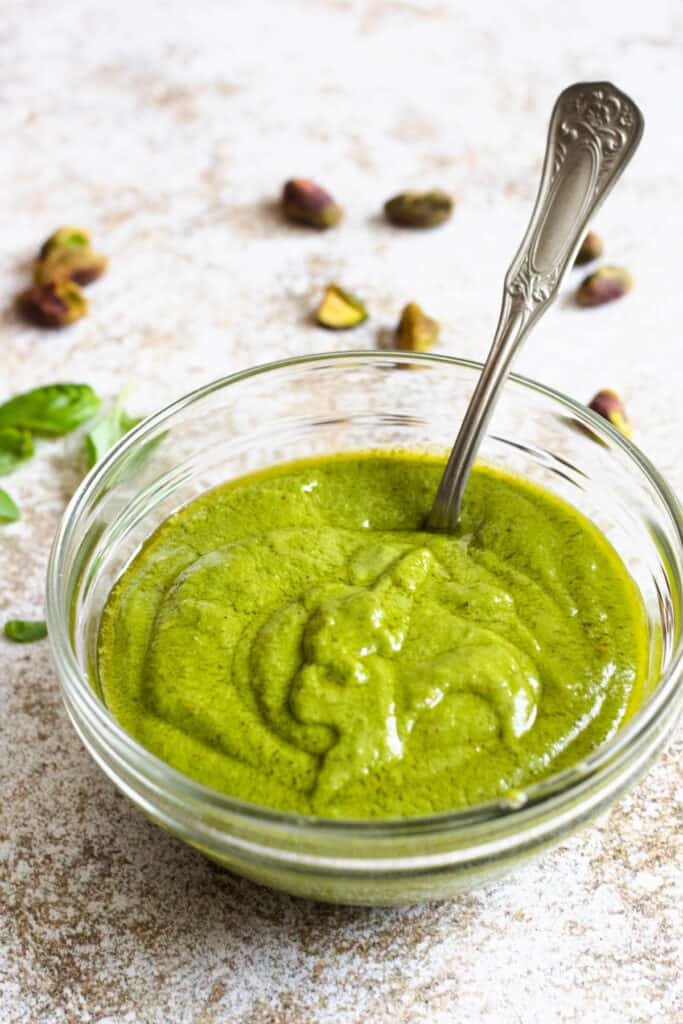 Bowl of pistachio pesto with a spoon in it