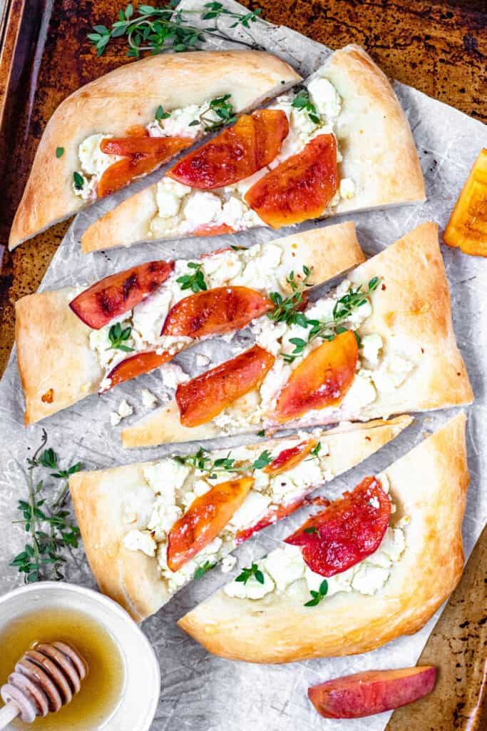 Peach pizza with goat cheese , thyme, and honey cut up on a baking sheet