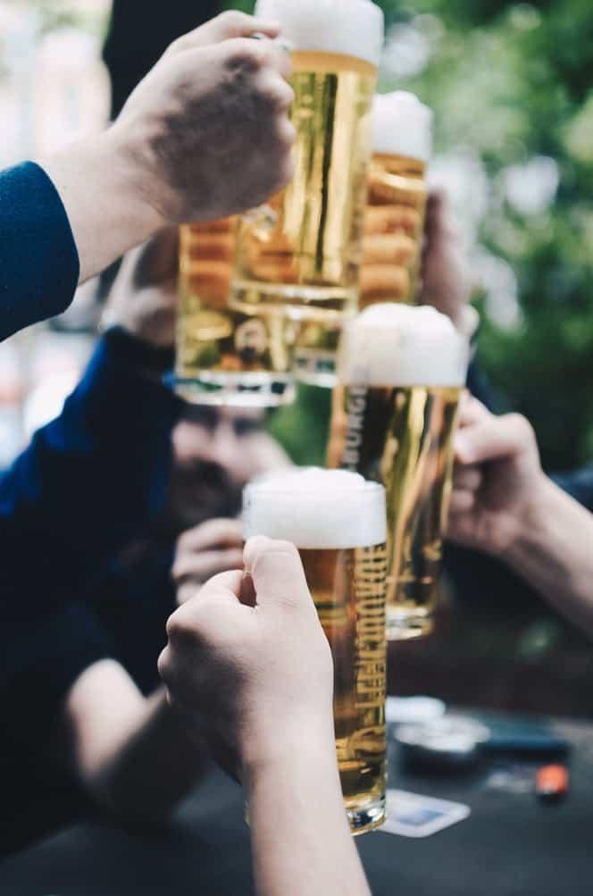 hands cheersing a beer