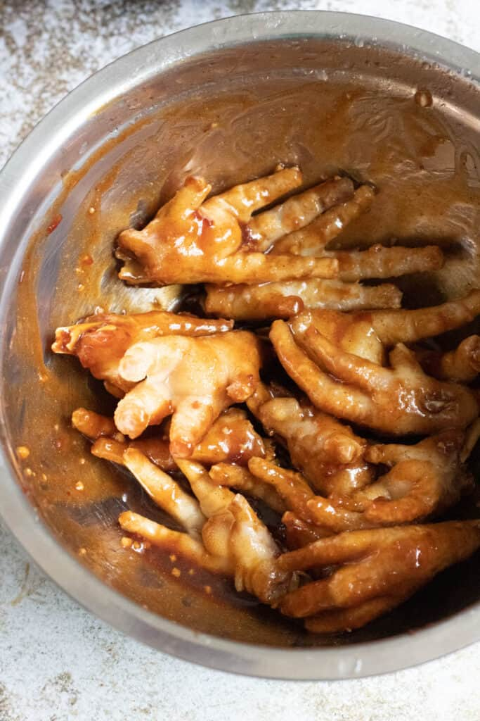 mixing bowl with chicken feet and sauce