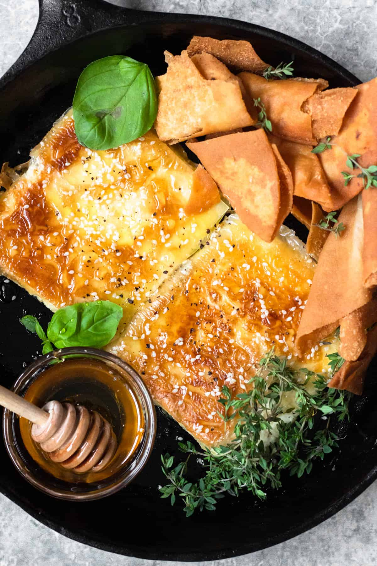 close up of feta cheese with pita chips and herbs