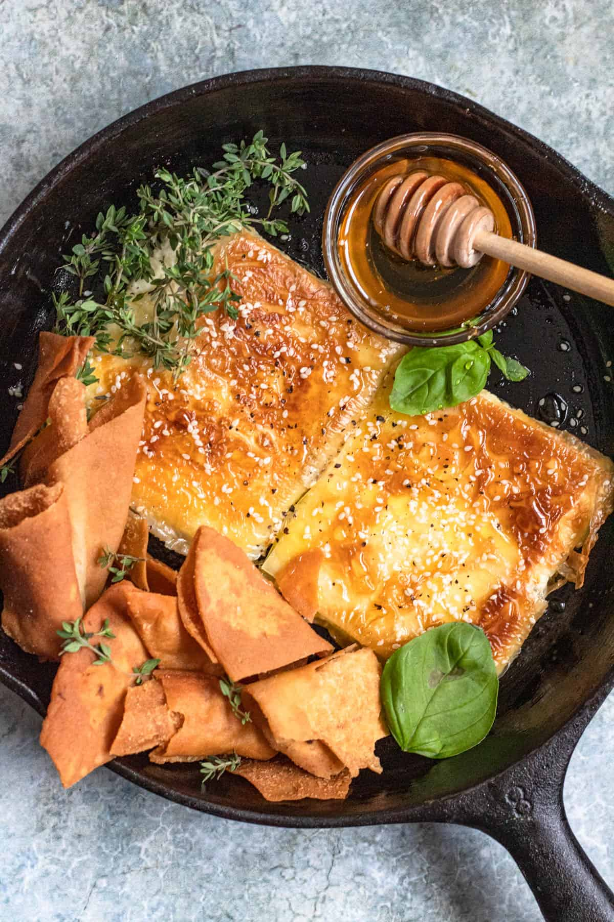 Fried feta in a cast iron skillet surrounded by honey, pita chips, and herbs