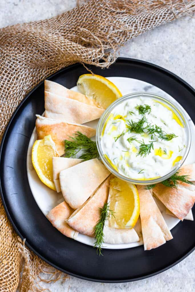 bowl of sauce surrounded by pita and lemon slices