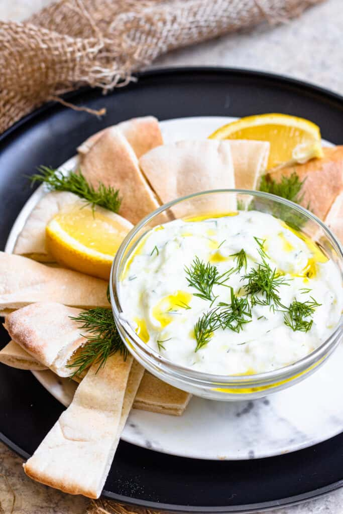 Bowl of tzatziki sauce sprinkled with dill and surrounded by pita