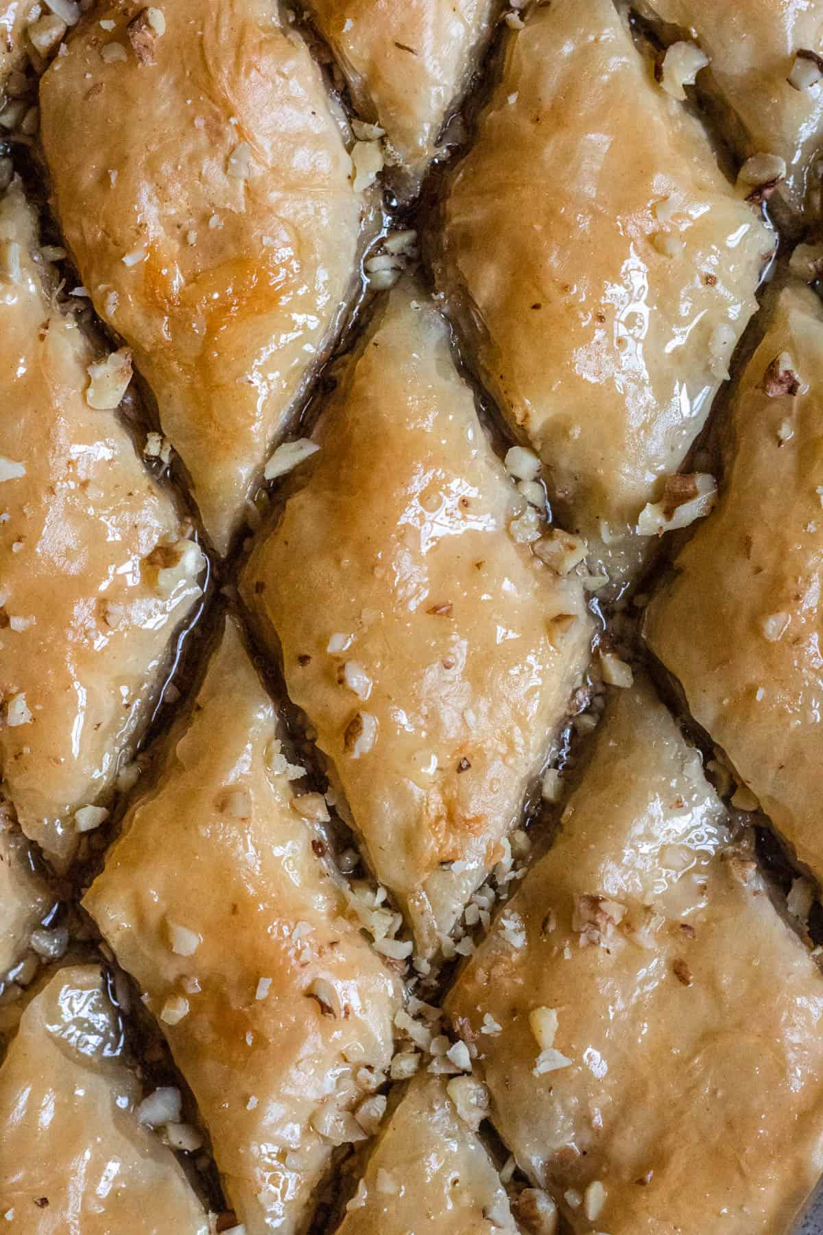 close up of pistachio baklava sprinkled with walnuts