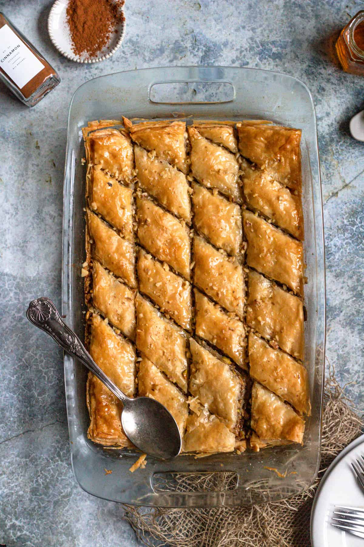 Full tray of pistachio baklava with a spoon across the top