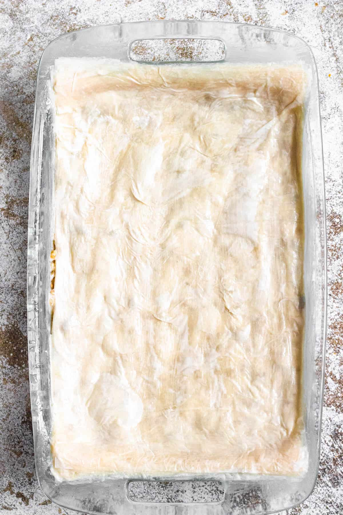 9x13 pan with layers of phyllo dough over the nut mixture