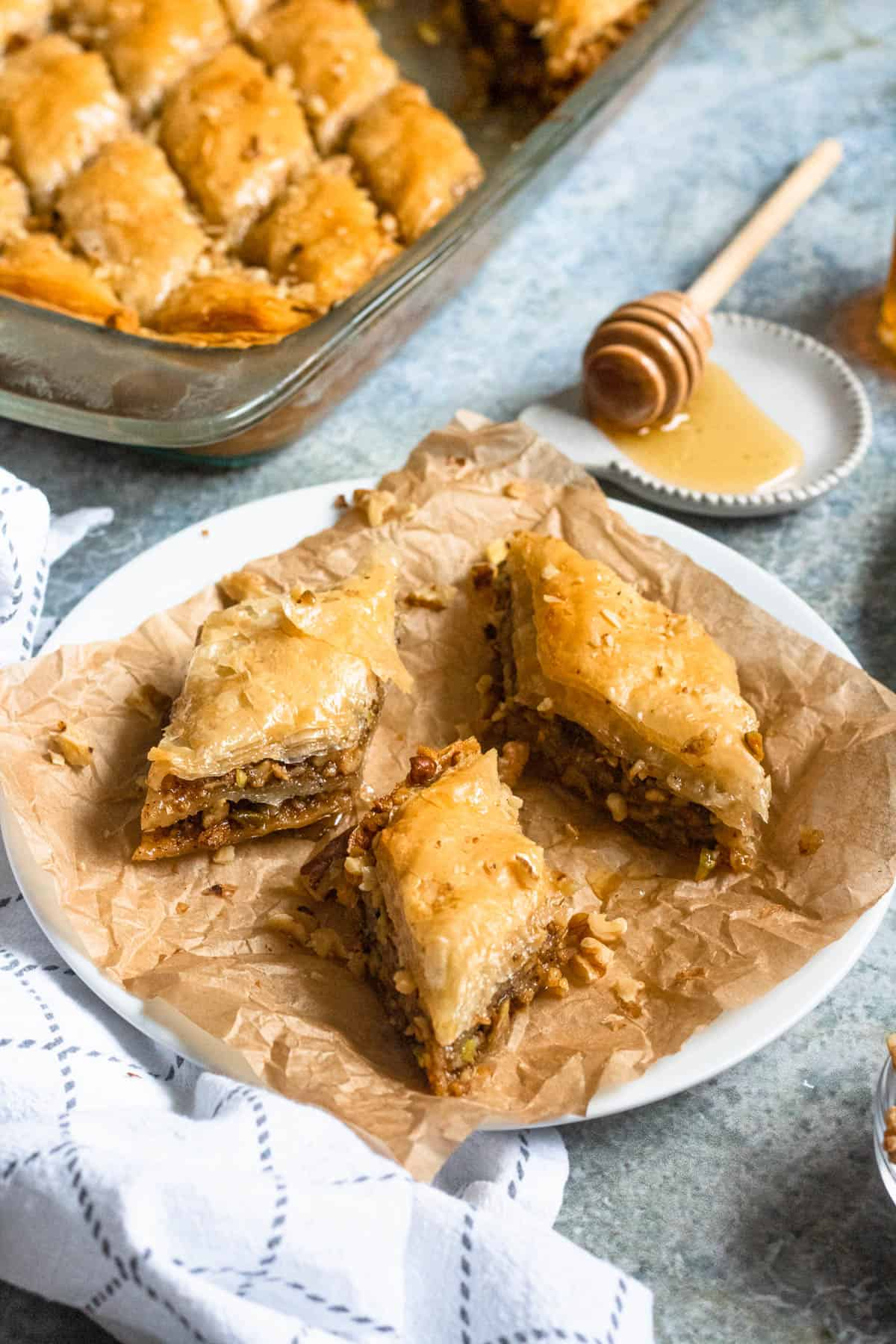 3 pieces of pistachio baklava with a tray of baklava behind it and a honey drip