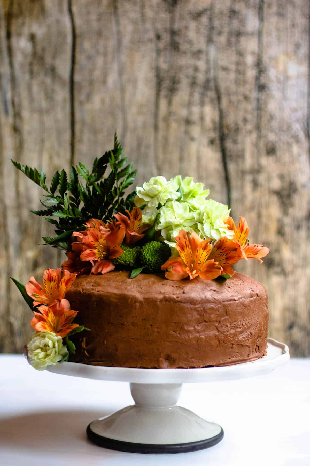 chocolate cake on a cake stand with lowers around it