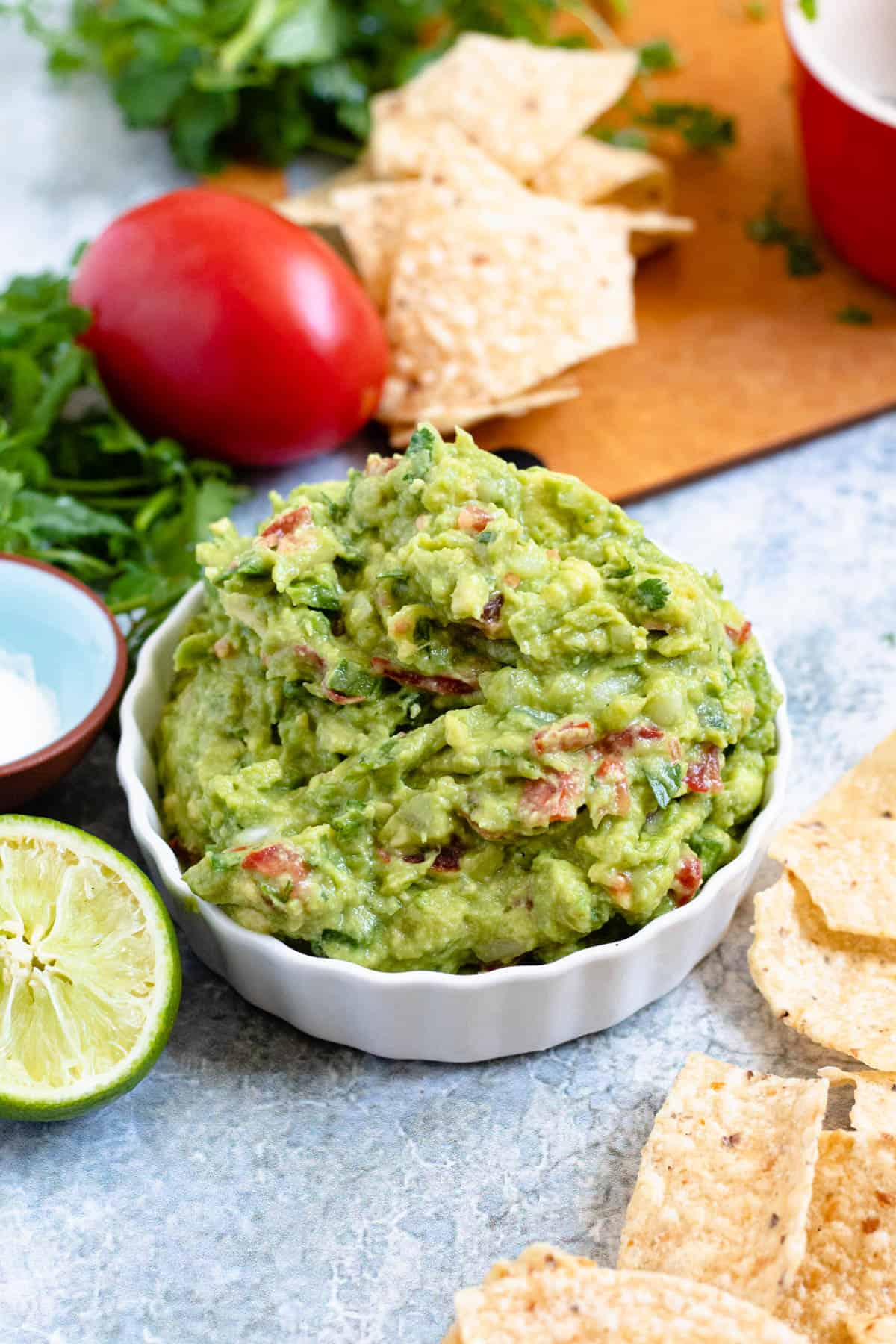 bowl of guacamole surrounded by chips, limes, salt, etc