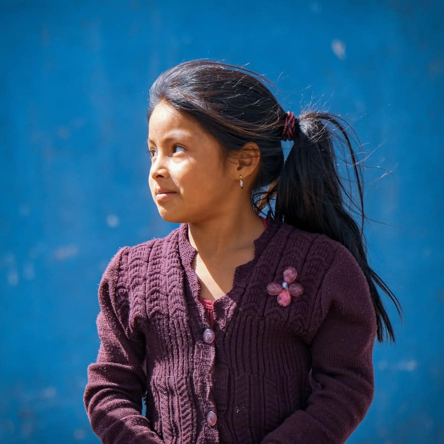 Mayan girl in a purple sweater in front of a blue wall