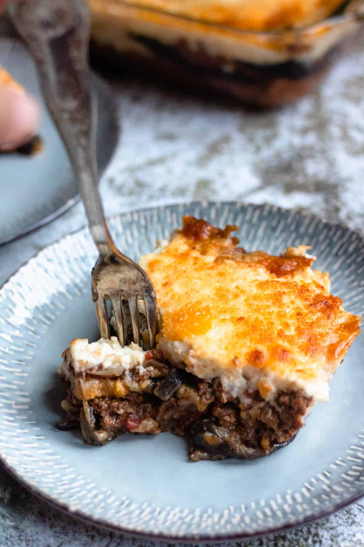 Fork taking a bite of moussaka off of a plate
