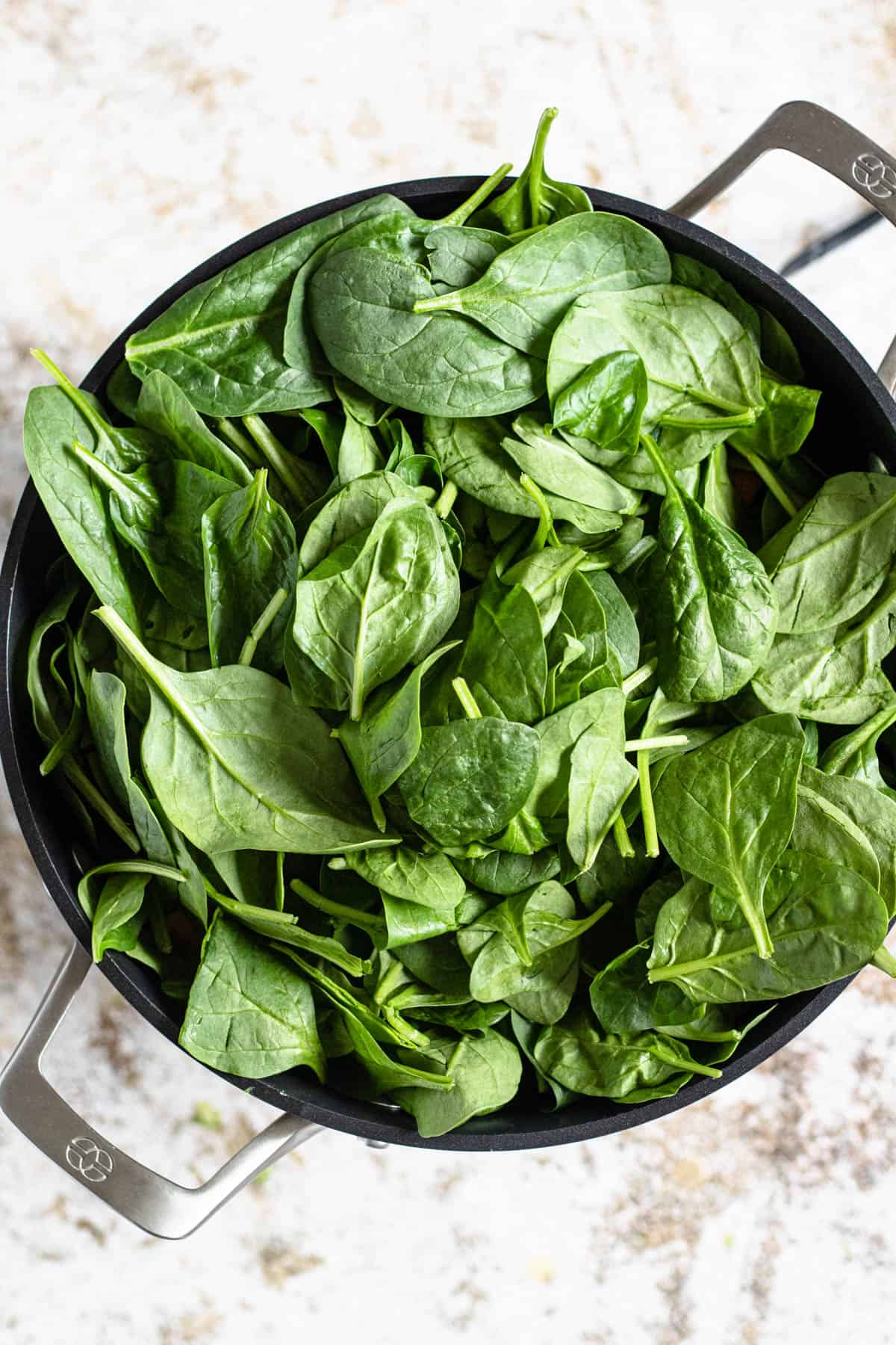 Oil down in a pot with spinach on top