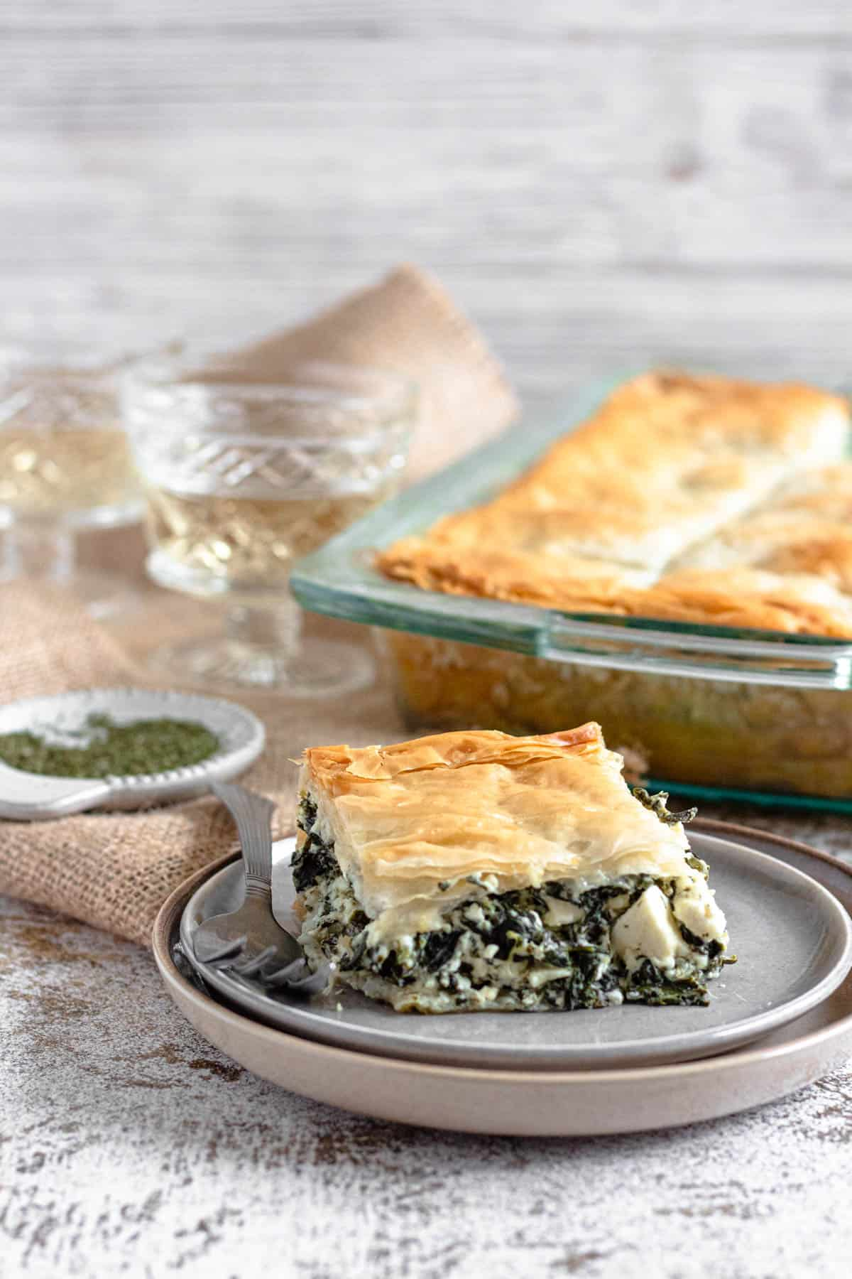 Front view of Spinach Pie with a tray of pie behind it