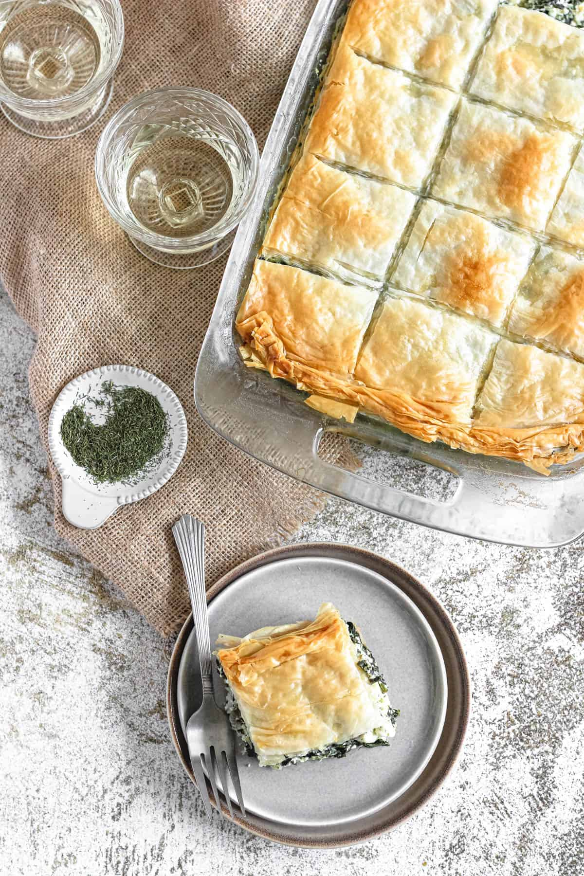 Spinach pie on a plate with a fork and a tray of spanakopita behind it