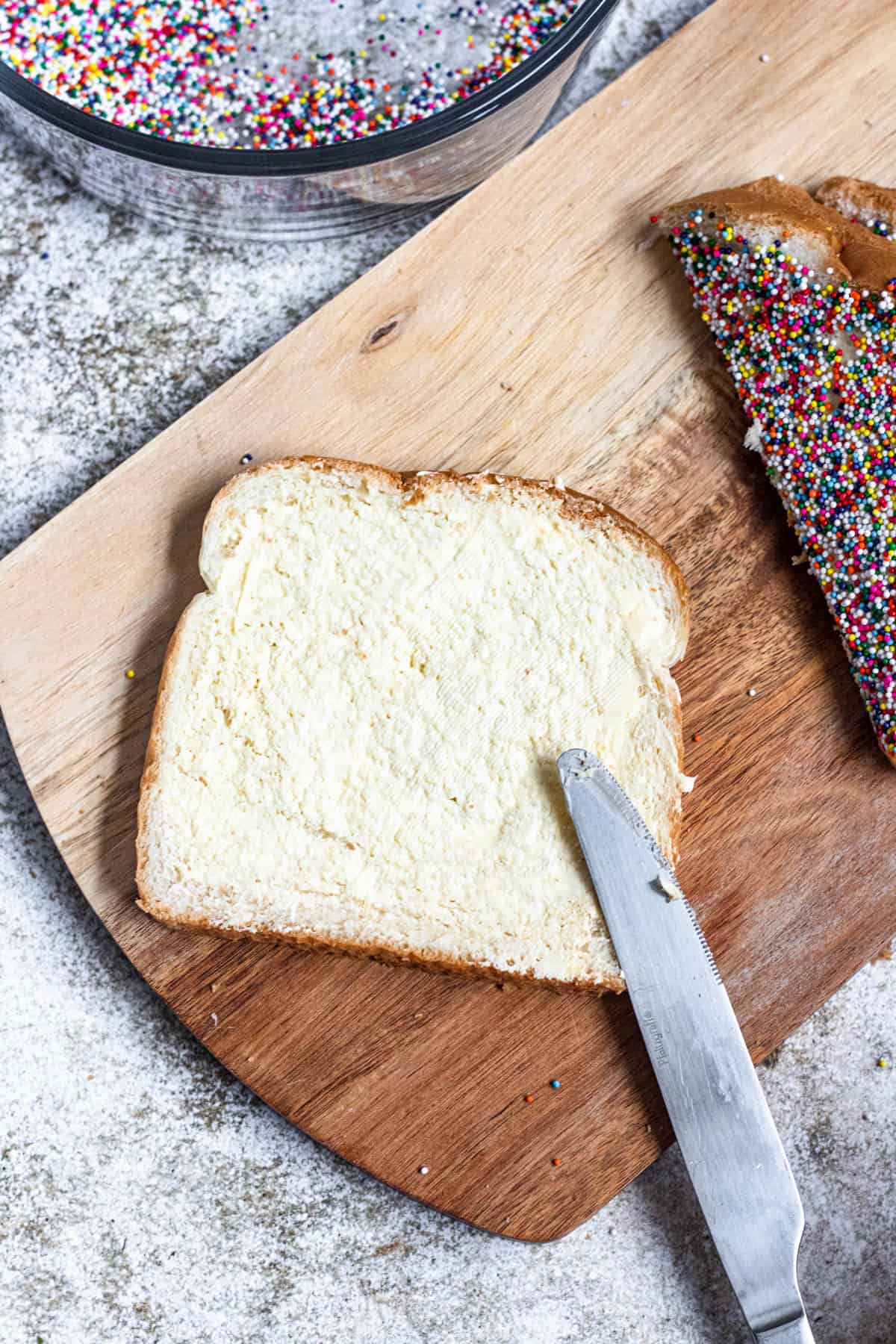 Butter knife spreading margarine on a piece of white bread