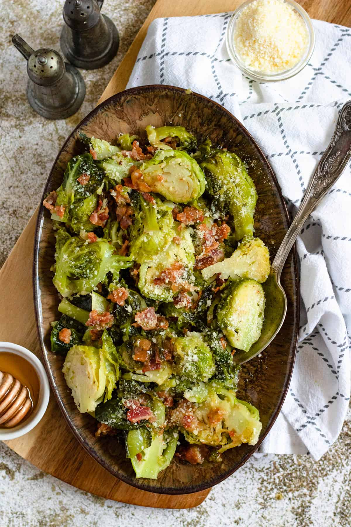 Bowl of Brussels sprouts with parmesan and a spoon