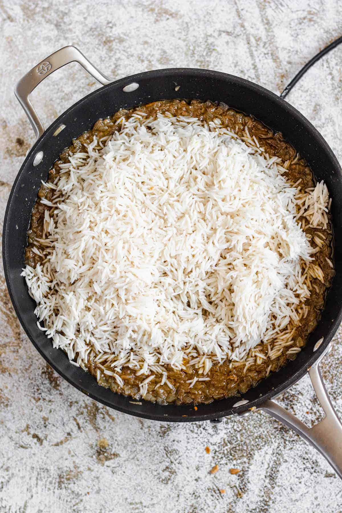 Large frying pan with lamb on the bottom and a mound of basmati rice on top