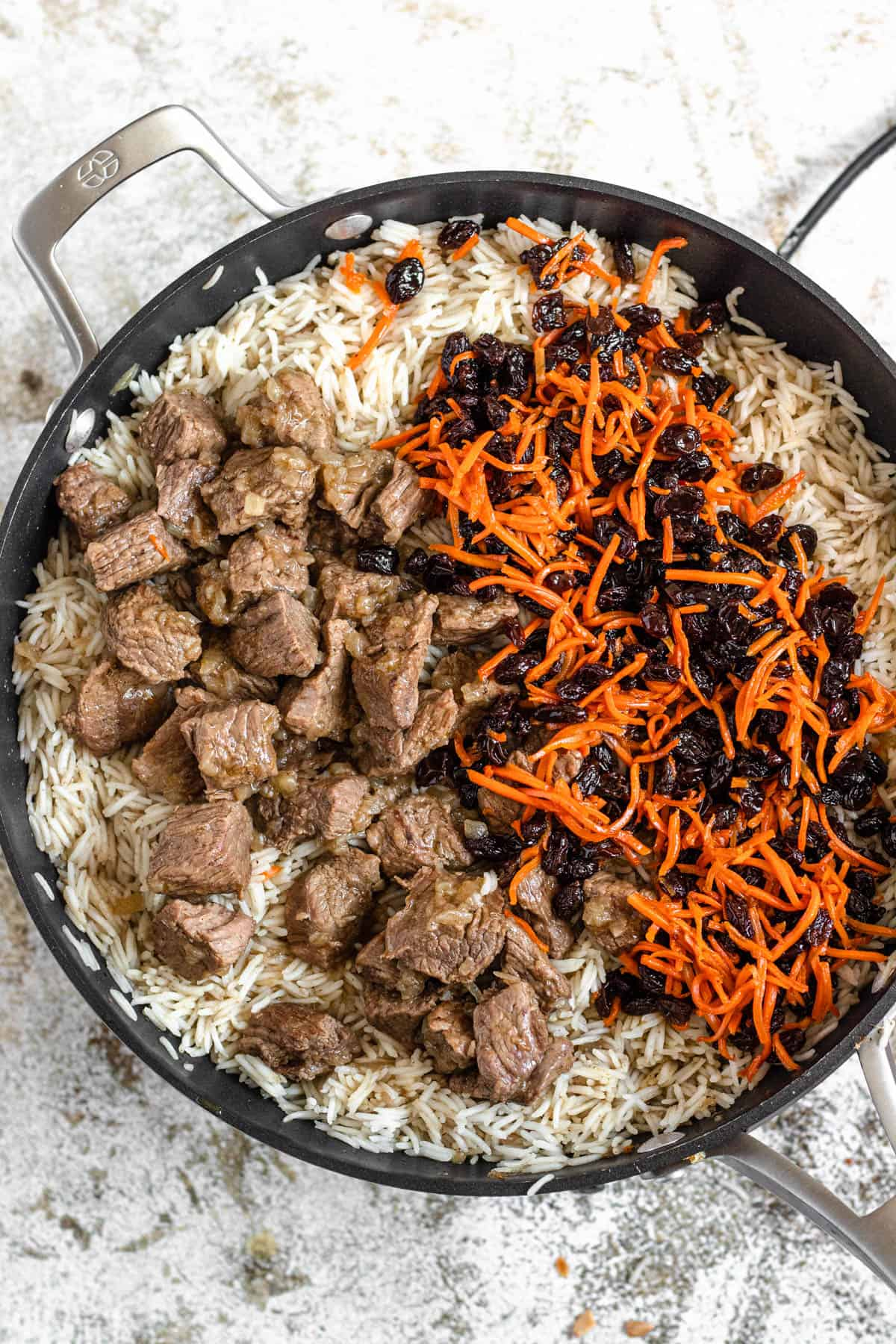 Large pan with cooked rice on the bottom and lamb meat, carrots, and raisins on top