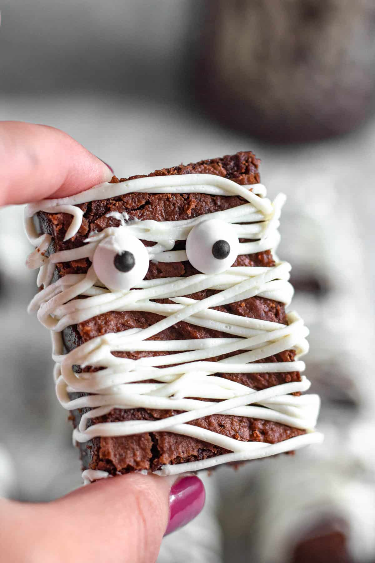 Hand holding a mummy brownie with candy eyes