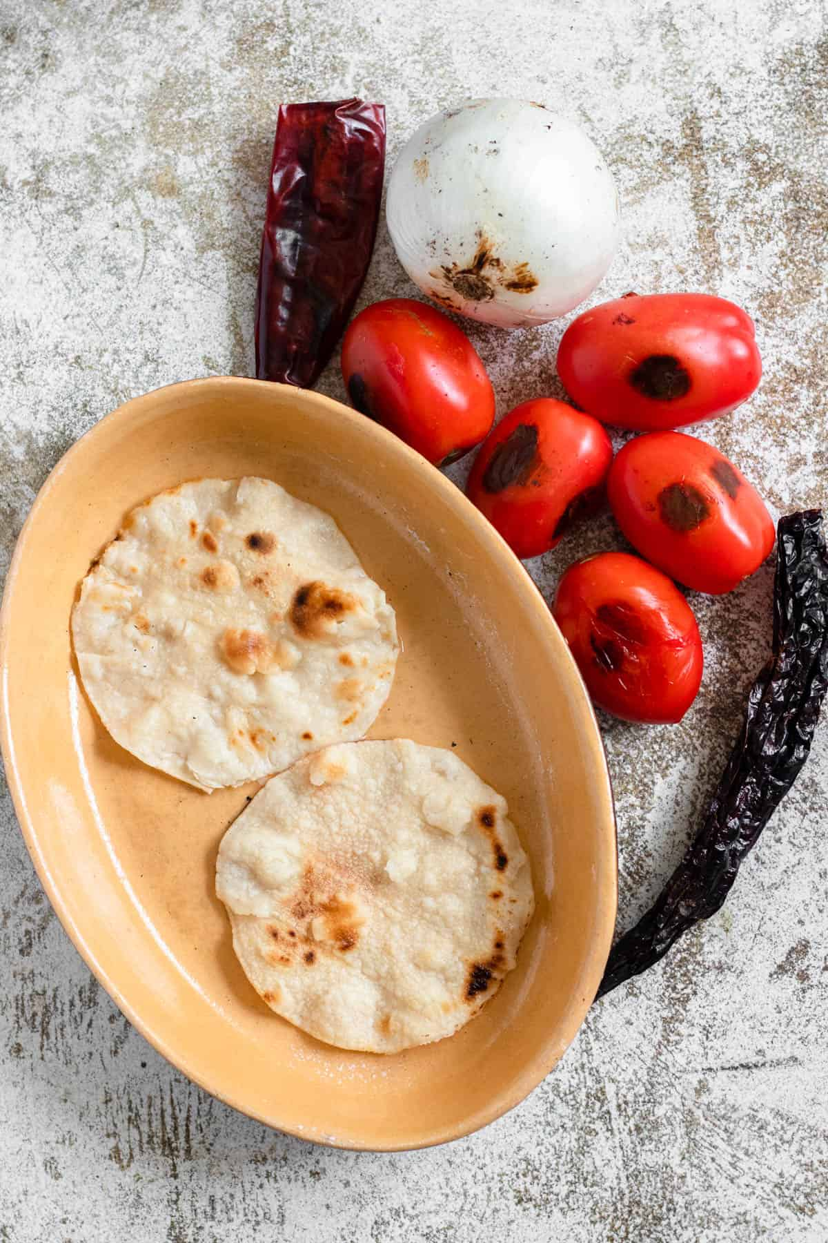 All charred ingredients -- tortillas, roma tomatoes, chiles, onions