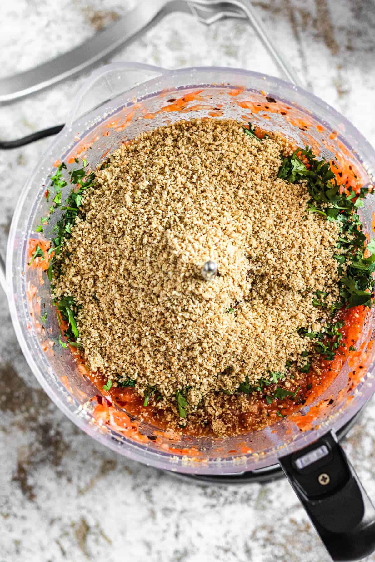 Food processor with blended tomatoes, cilantro, and ground sesame seeds