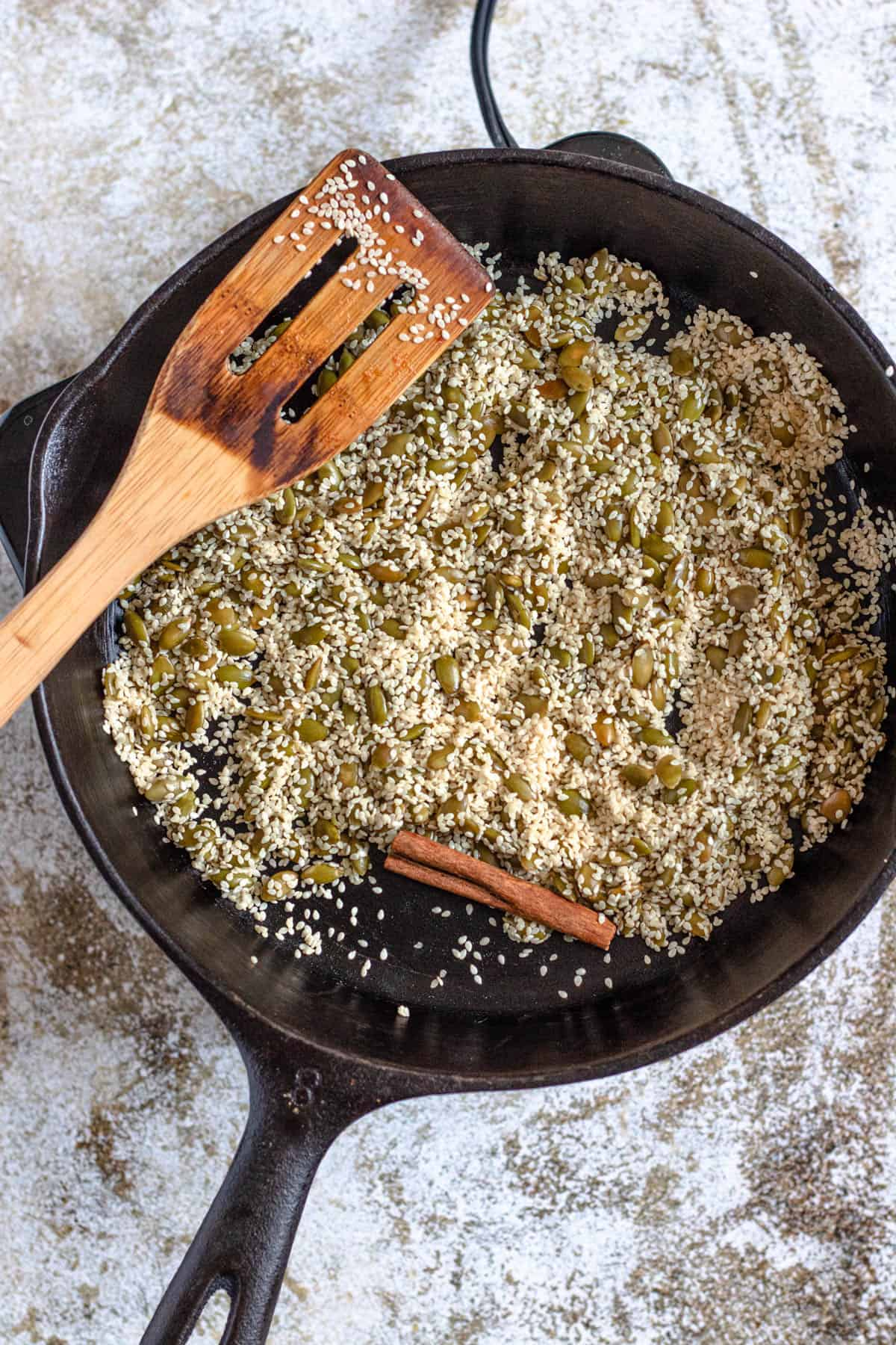 Toasted sesame seeds, pumkin seeds, and cinnamon in a skillet