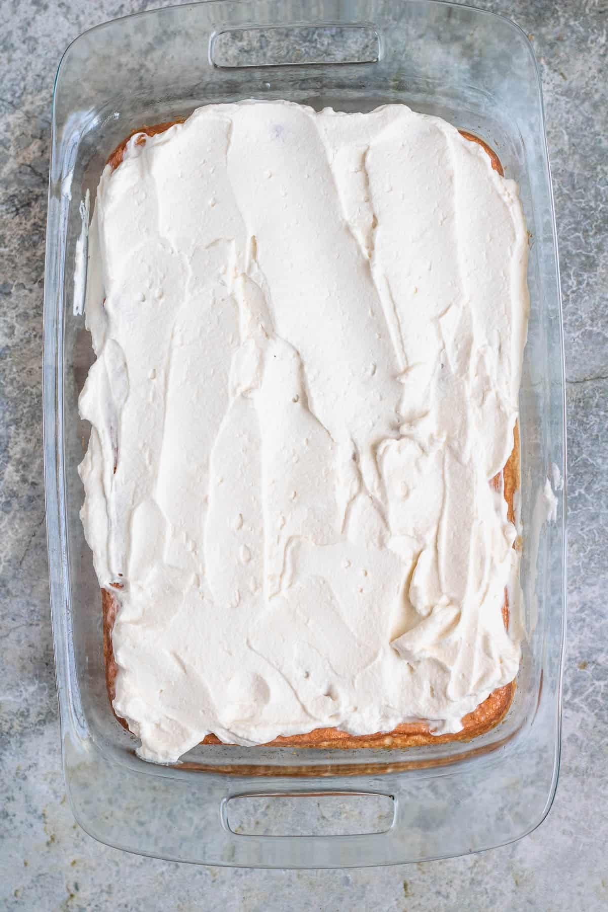 Whipped cream spread on the easy tres leches cake