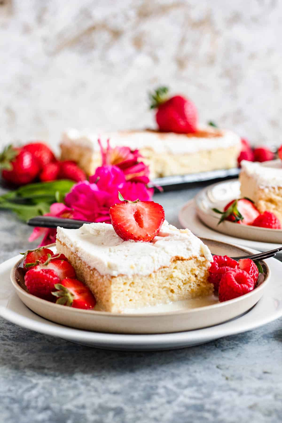 2 plates of Tres Leches cake with strawberries, raspberries, and flowers